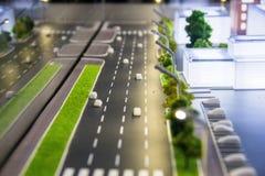 Teil eines Plans der Stadtstraßen, Straßen mit Autos, Gebäude, Abendbeleuchtung Stadtarchitekturmodell, maquette Stockbild