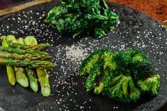 Teil gegrillter Spargel, gegrillter Brokkoli und Spinat auf einem runden Schwarzblech auf einem kupfernen Hintergrund stockfotos