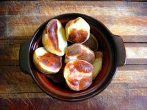 Teil Ofenkartoffeln in den großen Stücken in einem Tongefäß auf einem hölzernen Brett Stockfotos