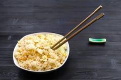 Teil von Fried Rice mit Essstäbchen auf dunkler Tabelle stockbild