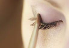 Teil weibliches Augenmake-up des Gesichtes, das mit Bürste zutrifft Stockbild