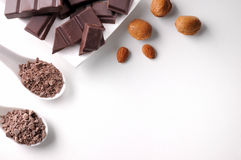Teile und Schokoladensplitter auf Behälter mit den Mandeln lokalisiert Lizenzfreie Stockbilder