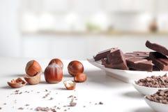 Teile und Schokoladensplitter auf Behältern mit Haselnüssen in der Ausrüstung Stockfoto
