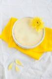 Teilen Sie den Käsekuchen ein, der mit gelber Blume, Draufsicht verziert wird Stockfotografie