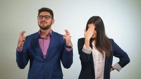 Teilhaber kreuzte ihre Finger, die das lustige Mädchen ihren Kollegen kritisiert, der Augen anhob glücklich seins geschlossen hat Stockbild