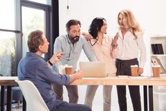 Teilhaber traten bei Tisch mit Laptop und Wegwerfkaffeetassen im Büro zusammen lizenzfreie stockfotos