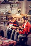 Teilnehmer der Band sitzend auf Sofa und Musikinstrumente spielend stockbild