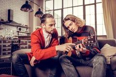 Teilnehmer der Musikband fühlend beschäftigt beim Spielen ihrer neuen Gitarre lizenzfreies stockbild