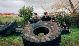 Teilnehmer an einen Hindernislauf, der ein Rad dreht lizenzfreie stockbilder