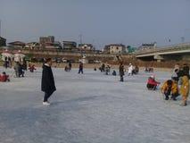 Teilnehmer-Eislauf auf dem gefrorenen Hwacheon-Fluss lizenzfreie stockbilder
