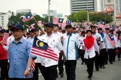 Teilnehmer-Wellenartig bewegen malaysische Flaggen während Malaysia-` s Unabhängigkeitstags Stockbild