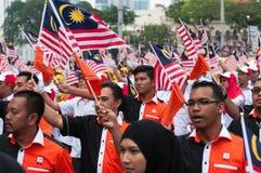 Teilnehmer-Wellenartig bewegen malaysische Flaggen während Malaysia-` s Unabhängigkeitstags Stockfoto