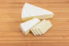 Teils geschnittene Brie auf hölzernem Schneidebrett stockbilder