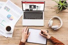 teilweise Ansicht des Mannes Anmerkungen im Notizbuch am Arbeitsplatz mit Laptop mit BBC-Website machend, Papiere, Tasse Kaffee stockfoto