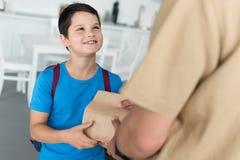 teilweise Ansicht des Vaters Papierpaket mit Nahrung gebend lächelndem Sohn mit Rucksack stockbild