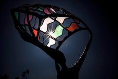 Teilweise Sonnenfinsternis glänzt durch die bunte Metallstatue lizenzfreie stockfotografie