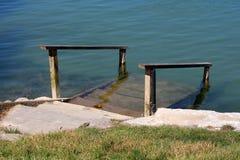 Teilweise versenkte hölzerne Schritte mit Handläufen auf dem Gras und konkreter Flussbank, die direkt in Wasser führen stockbild