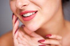 Teilweises Porträt der Frau lächelnd mit roter Maniküre und fehlerlosem Teint stockfoto
