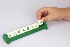 Teja de la letra del Scrabble del niño que pone Fotos de archivo