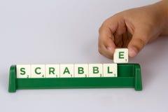 Teja de la letra del Scrabble del niño que pone Imágenes de archivo libres de regalías