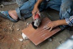 Teja del corte del trabajador de construcción del hombre con eléctrico foto de archivo libre de regalías