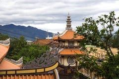 Tejado anaranjado de la pagoda budista con las montañas y la ciudad Foto de archivo libre de regalías