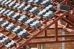 Tejado bajo construcción con las pilas de tejas de tejado para la estructura casera Imagen de archivo libre de regalías