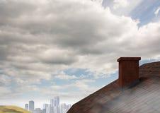 Tejado con la chimenea en cielo del país y de la ciudad Fotos de archivo