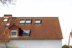 Tejado de casas residenciales clásicas con las tejas de techumbre anaranjadas y Imagen de archivo libre de regalías