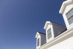 Tejado de la casa y de Windows contra el cielo azul profundo fotos de archivo