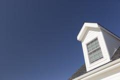 Tejado de la casa y de Windows contra el cielo azul profundo fotografía de archivo