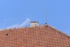 Tejado de las tejas de la arcilla con la chimenea Foto de archivo libre de regalías