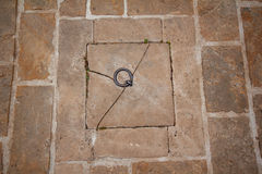 Tejado de piedra, anillo oxidado en medio de las pavimentadoras viejas imagenes de archivo