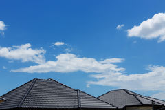 Tejado de teja negro en casa con el cielo azul y la nube claros Fotos de archivo libres de regalías