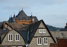 Tejado de varias casas con ventanas agradables y una torre detrás imagenes de archivo