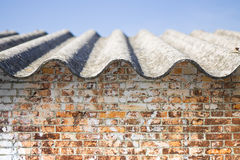 Tejado del amianto sobre una pared de ladrillo vieja Fotografía de archivo