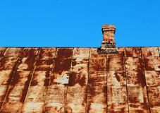Tejado oxidado viejo del metal con la chimenea del ladrillo contra el cielo azul Fotografía de archivo