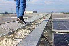 Tejado solar del picovoltio con el técnico Walking en la calzada foto de archivo libre de regalías