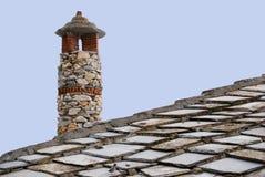 Tejado y chimenea de la casa hechos de piedras Imagenes de archivo