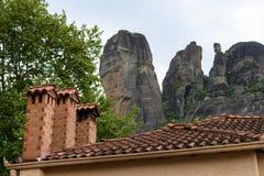 Tejado y chimeneas de teja con las rocas de Meteora, Grecia en fondo imagen de archivo libre de regalías