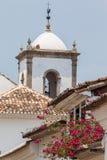 Tejados antiguos con una torre de iglesia vieja en el fondo Fotografía de archivo