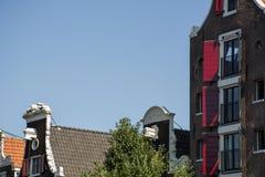 Tejados de las casas viejas de Holanda con los obturadores y el cielo azul Imágenes de archivo libres de regalías