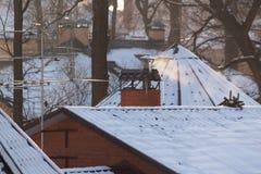 Tejados del invierno con nieve y humo el día soleado Fotos de archivo libres de regalías