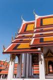 Tejados rojos y anaranjados contra un cielo azul marino en el palacio magnífico, Tailandia Fotos de archivo