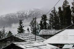 Tejados y árboles Nevado con la montaña hermosa cubierta en niebla foto de archivo libre de regalías