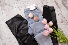 Tejanos y polainas de cuero negras, vidrios, tulipanes rosados concepto de moda Visión superior foto de archivo