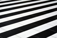 Tejas blancos y negros en el piso Foto de archivo