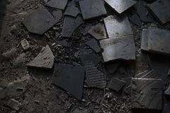 Tejas, cajas del cigarrillo y extremos de cigarrillo quebrados en el piso Imagen de archivo