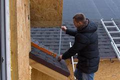 Tejas de medición del Roofer en una nueva casa foto de archivo libre de regalías