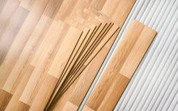 Tejas del piso laminado con el efecto de madera que pone en la espuma baja blanca, listas para ser instalado fotos de archivo